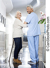 oude vrouw, met, stok, en, fysiotherapeut, staand, in,...