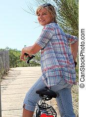 oude vrouw, rijden van een bike