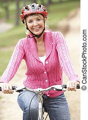 oude vrouw, rijdende fiets, in park