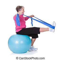 oude vrouw, stretching, het uitoefenen van materiaal