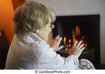oude vrouw, verwarmende handen, door, vuur, thuis