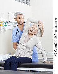oude vrouw, wezen, geassisteerd, door, fysiotherapeut, met, arm, oefening