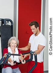 oude vrouw, wezen, geassisteerd, door, trainer, in, gebruik, het roeien machine