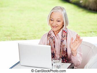 oude vrouw, zwaaiende , terwijl, video conferencing, op, draagbare computer