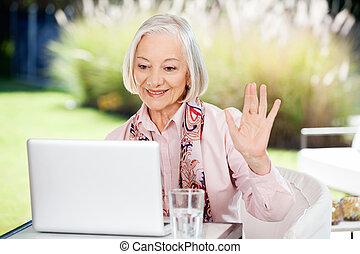 oude vrouw, zwaaiende , terwijl, video, kletsende, op, draagbare computer