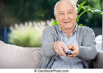 oudere man, gebruik, afstandsbediening, terwijl, zitten op bank
