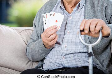 oudere man, het tonen, vier azen, terwijl, zittende