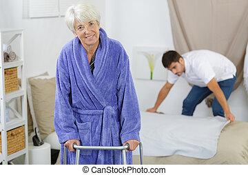 oudere vrouw, ambulates, van, haar, bed, met, een, walker