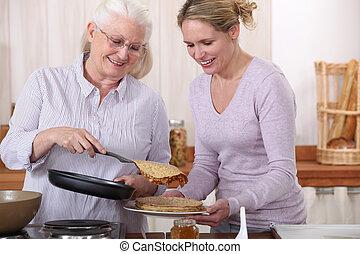 oudere vrouw, en, dochter, met, pannekoekjes