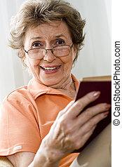 oudere vrouw, ontspannend thuis, het lezen van een boek