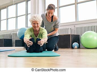 oudere vrouw, wezen, hielp, door, haar, instructeur, in de gymnastiek