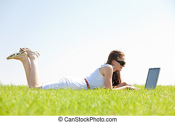 oung female lying on the grass in the park using a laptop