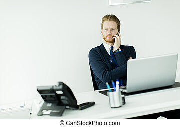 oung redhair man talking on mobile phone in the office