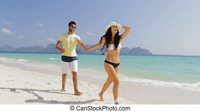 ?ouple Walking On Beach Talking, Girl Leading Man Holding...