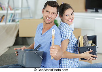 ouple with brushes on hands looking at the camera