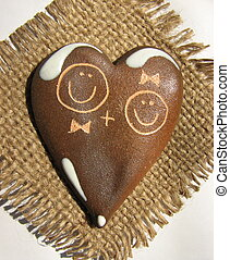 Clay heart with faces of boy and girl graven on its surface