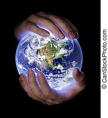 Our Planet Earth - Man holding a glowing earth globe in his...