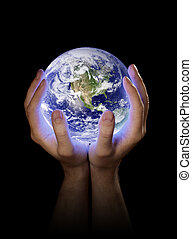 Our Planet Earth - Man holding a glowing planet earth in his...