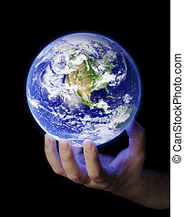 Our Planet - Man holding a glowing earth in his hand. Earth...