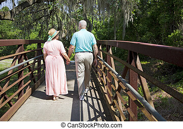 Out For a Stroll - Senior couple holding hands and strolling...