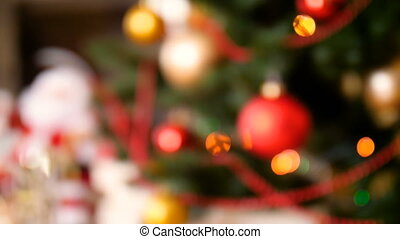 Out of focus 4k footage of beautiful decorated christmas tree with baubles and colorful lights in living room