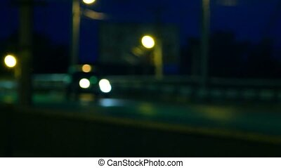 Out of focus background with blurry unfocused driving cars and street lights.