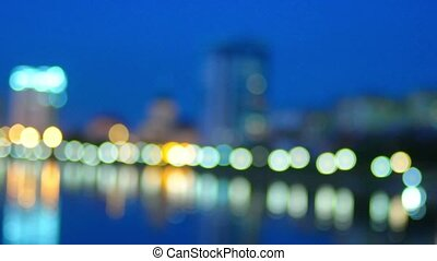 Out of focus city night lights reflection in river. Bokeh defocused urban scene