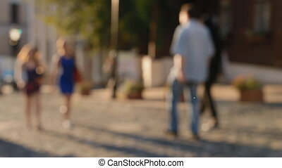 Out of focus footage. People walk down the street.