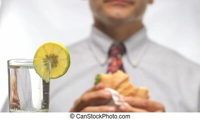 out of focus man in tie with sandwich