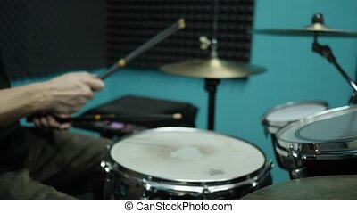 Out of focus shot of drummer playing on a drum kit. Musician...