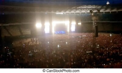 Out of focus video of brightly lit scene on concert at big...