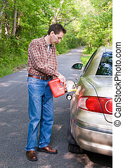 Out of Gas - A man pouring gasoline into the gas tank of his...