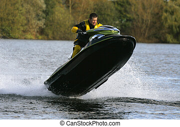 Out of the water - A jet ski and its rider leaping out of...