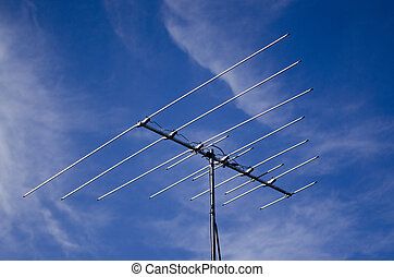 Outdated analogue tv antenna against blue sky.