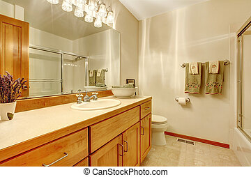 Simple white bathroom with wood cabinets,