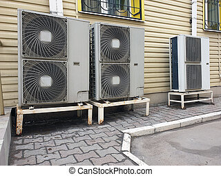 outdoor air conditioning units of office space attached to facade of building