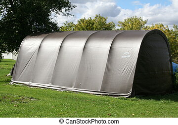 Temporary garage shelter used for storage in a yard