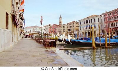 Small outdoor cafe by channel and long wooden gondolas drifting on still high tide water and lonely passers-by in Venice city