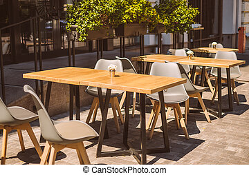 Outdoor cafe terrace with wooden furniture