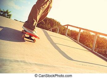 outdoor; calf; sunlight; ramp; skating; dynamic; people; female; concrete; energy; youth; skateboarder legs skateboarding at skatepark ramp