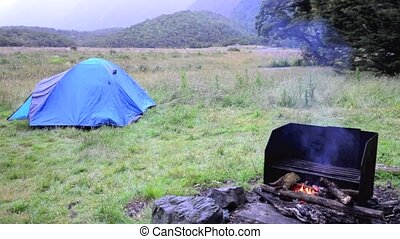 Outdoor campfire - An outdoor campfire near a tent in a ...