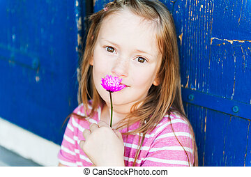 Outdoor close up portrait of a 7 years old girl with pink flower