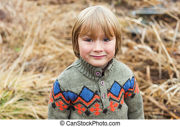 Outdoor close up portrait of a cute little boy of 4-5 years old, playing by the lake on a cold day
