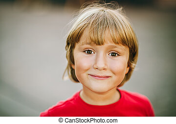 Outdoor close up portrait of adorable 6 year old kid boy, candid facial expression