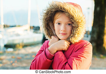 Outdoor close up portrait of cute 9-10 year old little girl wearing warm winter jacket with hood and fur
