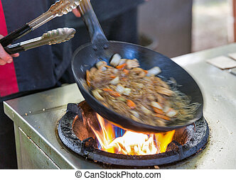 outdoor cooking asian food in a wok