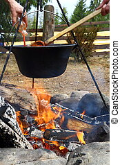 outdoor cooking in cauldron over the fire