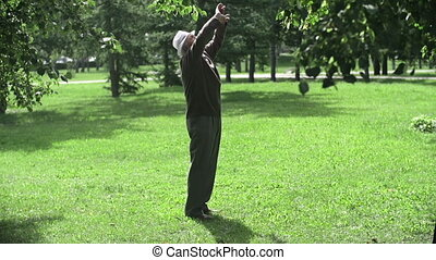 Outdoor Exercising - Static camera shot of senior man doing...