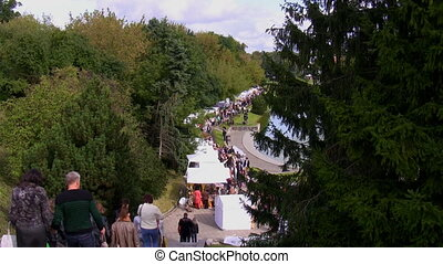 People climbing down stairs towards outdoor fair in the park on the lake side