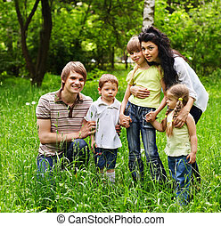 Outdoor family with kids on green grass.